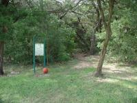 The trailhead resides near a baseball diamond in the park.