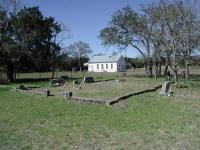 The Bolt family section of the cemetery includes a concrete block boundary around its perimeter.  Note the Nameless school house in the background.
