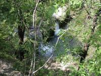 Although the trail parallels Bull Creek for some distance, the dense foliage provides just a few glimpse of the water below, such as this one of the dam.