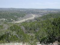 The trail around Wolf Mountain looks down upon the Pedernales River valley below.