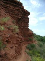 The trail hugs some of the red siltstone and sandstone formations near the river.