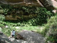 Austin Explorer stands on some boulders under the grotto near Fern Cave.