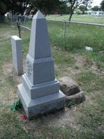 The new Sam Bass marker sits directly in front of the original, chipped tombstone.