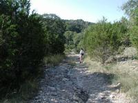 The trail surface varies from grassy and flat to rocky and steep conditions.